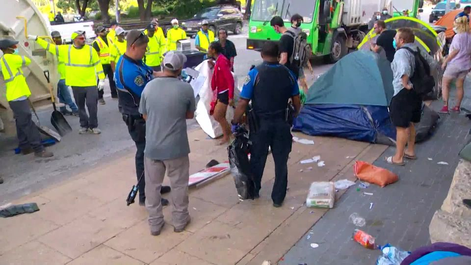 People clashed with crews cleaning up homeless tents outside Austin City Hall M...